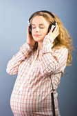 Beautiful pregnant blonde listens to classical music on headphones. Portrait of pregnant woman. The development of the child in the womb — Stok fotoğraf