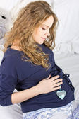 Beautiful pregnant blonde stroking her belly — Stock Photo