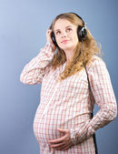 Young pregnant woman listening to music on headphones at home closed. Portrait of pregnant woman — Foto de Stock