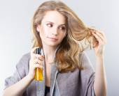 Beautiful curly blonde takes care of her hair.Beautiful woman thinking about hair. Dry hair treatment, moisturizing, therapy — Stock Photo