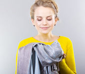 Young blonde with clothes in hands.Hostess thinks how to save clothes. Means for care of clothes, washing powder, conditioner for clothes. Shopping — Stock Photo