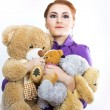Young girl with a bunch of stuffed animals. Girl with soft toys on a white background — Stock Photo #64999583