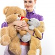 Young girl with a bunch of stuffed animals. Girl with soft toys on a white background — Stock Photo #64999589