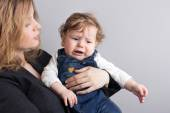 The child is crying on the mother's arms.Portrait of mother and son. maudlin child — Foto Stock