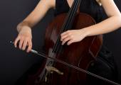 A young girl plays the cello in the dark. Hands on cello — Stock Photo
