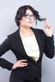 Zakenvrouw in een smalle zwarte jas. Succesvolle vrouw. Mooie brunette. Portret van een mooi meisje in glazen — Stockfoto
