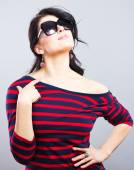 Beautiful brunette in a blue dress with red stripes. Fashion. Portrait of a young girl in sunglasses. — Stock Photo