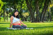 Beautiful pregnant asian woman reading the book in the park — Stock Photo