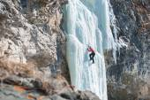 Climber ascends the vertical icefall — Stok fotoğraf