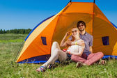 Outdoor portrait of a happy couple in love near the tent on the — Stock Photo