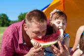 Father and daughter eating watermelon at the picnic — Stok fotoğraf