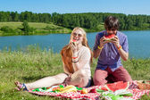 Outdoor portrait of happy loving couple at the lake, which is eating watermelon — Stock Photo