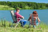Outdoor portrait of happy couples at the lake, sitting in a chai — Stock Photo