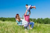 Outdoor portrait of a happy family. father picked up the child  in her arms — Stock Photo