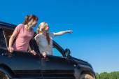 Outdoor portrait of young girls, looking out the window black car — Stock Photo