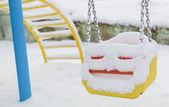 Pokryte śniegiem huśtawka na placu zabaw w zimie — Zdjęcie stockowe