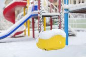 Snow covered swing and slide at playground in winter — ストック写真