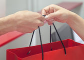 Customer receiving shopping bag from cashier — Stock Photo