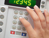 Woman entering security code to alarm system — Stock Photo