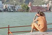 Indian sadhu (holy man) sits near the Ganges, Haridwar, India. — Stock Photo