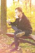 Young attractive man a black jacket in autumn park — Stock Photo