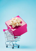 Shopping cart with large gift — Stock Photo