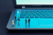 Miniature figures walking on a laptop — Stock Photo
