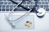 Pills and stethoscope on laptop — Stock Photo