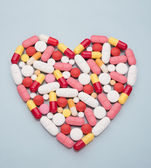 Pills and capsules in heart shape — Stock Photo