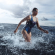 Young woman athlete running out of the water — Stock Photo #66083423