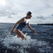 Young woman athlete running out of the water — Stock Photo #66083439