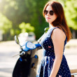 Young woman standing next to the scooter — Stock Photo #78370930