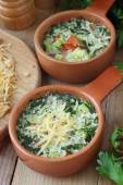 Omelette with cheese, vegetables and herbs cooked by steaming in ceramic pots — Stock Photo
