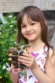 Smiling little girl holding a russian tortoise. Loving nature concept — Stock Photo