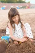 Cute little girl making sand castle on river beach. Femininity concept — Stock Photo