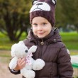 Toddler boy in brown coat and knitted bear hat with toy bear in his hands outdoor in autumn — Stock Photo #58318995