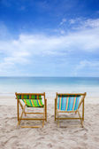 Beach chairs on the white sand beach with cloudy blue sky — Stock Photo