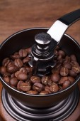 Coffee beans on the brown grinder wooden background — Stock Photo