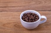 Cup of coffee beans on the brown wooden background — Stock Photo