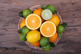 Mix of fresh citrus fruits in basket on wood — Stock Photo