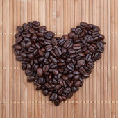 Coffee beans in shape of heart on wood — Stock Photo