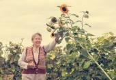 Senior mujer sonriendo a un girasol — Foto de Stock