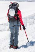 Female mountaineer ascending a glacier. — Stock Photo