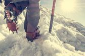 Close up of hiking shoes with crampons and ice axe. — Stock Photo