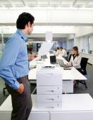 Worker with copy machine in office — Stock Photo