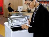Businesswoman using copy machine — Stock Photo