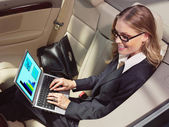 Businesswoman in her car with laptop — Stock Photo