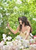 Mooie vrouw zitten in een mooie bloementuin en kijken in de verte — Stockfoto