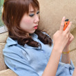 Portrait of young beautiful woman sitting on sofa and playing with her mobile phone — Stock Photo #52003085