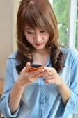 Portrait of young beautiful woman playing with her mobile phone — Stock Photo